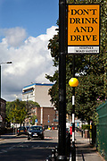 Car approaching a Don't drink and drive sign in Stepney, East London. This is a public information warning sign in an area prone to drinking and driving offences.