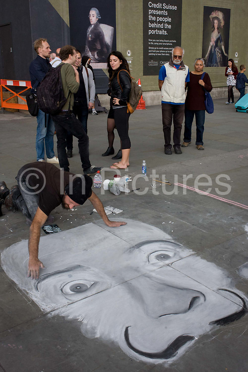 A street artist works on his pavement piece in front of Goya portraits, sponsored by Credit Suisse and advertised on a construction hoarding outside the National Portrait Gallery. Creating his version of a Salvador Dali face on the ground, the artist chalks and smooths the features of the famous Spanish surrealist.  <br /> Salvador Dalí was a prominent Spanish surrealist painter born in Figueres, Catalonia, Spain. He was a skilled draftsman, best known for the striking and bizarre images in his surrealist work. Francisco José de Goya y Lucientes 1746 – 1828 was a Spanish romantic painter and printmaker regarded both as the last of the Old Masters and the first of the moderns. In a scene of contemporary street art and that of high culture, we see a man trying to make a living outside versus a man who once did the same in another era.