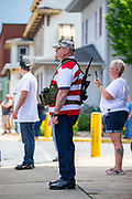 """Watsontown, PA (June 28, 2020) -- An armed counter protester watches a Black Lives Matter protest across the street. About 200 people demonstrated and marched in support of Black Lives Matter. They were confronted by nearly 50 counter-protesters who shouted """"all lives matter,"""" """"blue lives matter"""" and called protesters communists. Local anti-racist activist group """"If Not Us, Then Who?"""" organized the event."""