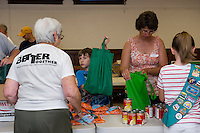 "Volunteers Judy Nelson, Xander Ainsworth, Tina Batchelder and Lacie Houle fill ""Got Lunch"" bags on Week 1 at the Congregational Church Monday morning.  (Karen Bobotas/for the Laconia Daily Sun)"