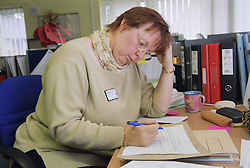 Woman working on Surviving Homelessness project writing notes at desk in office,