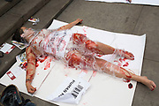 London, UK. Saturday 15th June 2013. Protesters wrapped in cellophane labelled HUMAN MEAT and covered in fake blood, to demonstrate against cruelty to animals in Britain's slaughterhouses. Calling for a slaughterhouse ban and to look at the term 'humane slaughter' in abattoirs, they recount stories of how animals are mistreated.