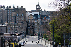 Edinburgh, Scotland, UK. 1 May 2020. Views of Edinburgh as coronavirus lockdown continues in Scotland. Streets remain deserted and shops and restaurants closed and many boarded up. Pictured;  Normally busy street full of tourist tour buses leading to the Old Town is deserted apart from a lone man. Iain Masterton/Alamy Live News