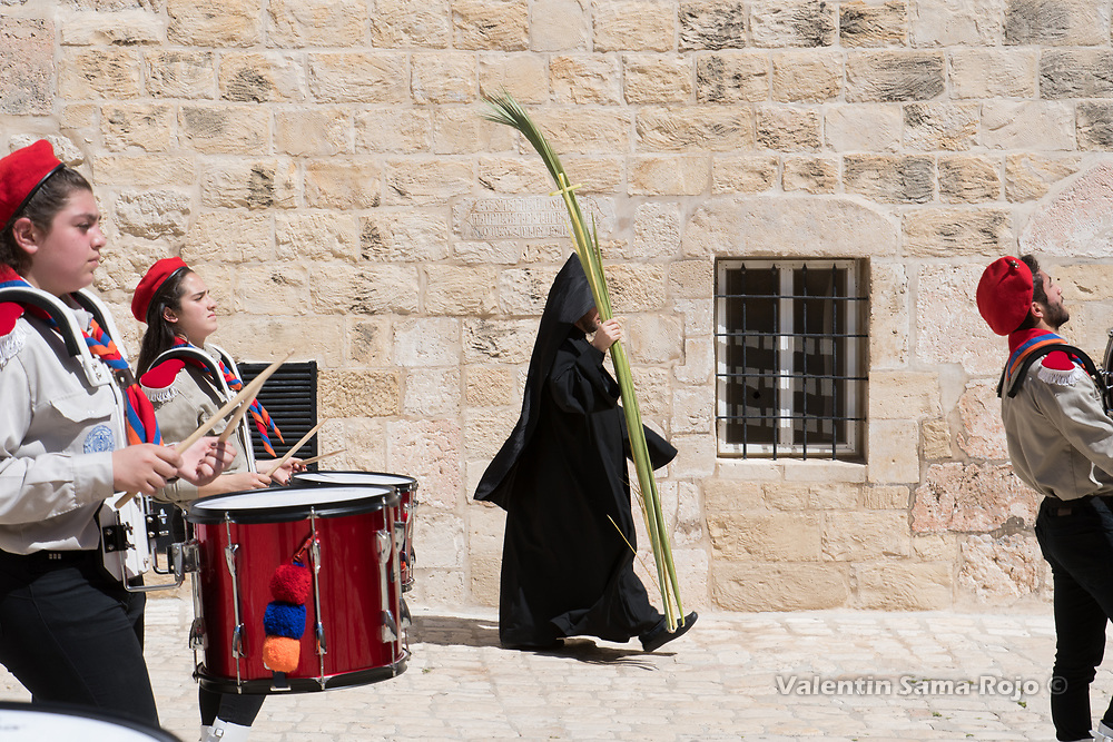 Jerusalem, Israel. 1st April, 2018. An Armenian monk walking with a palm tree leaf while the Armenian Scout Troop music band plays at the Armenian compound after Armenian Palm Sunday procession. © Valentin Sama-Rojo.