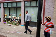 08072019 - Dayton, Ohio, USA: A man walks past a memorial in front of a building on 5th Street at the site of Sunday morning's mass shooting that left 9 dead, and 27 wounded, Wednesday, August 7, 2019 in Dayton, Ohio. Trump visited a nearby hospital but did not visit the site of the shooting before flying to El Paso, Texas, which was also the site of a mass shooting.