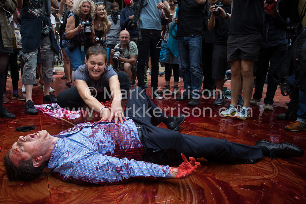 An environmental activist from Extinction Rebellion dressed as a financier covers himself in fake blood during a mass civil disobedience event in Paternoster Square following a Blood Money March through the City of London on 27th August 2021 in London, United Kingdom. Extinction Rebellion were intending to highlight financial institutions funding fossil fuel projects, especially in the Global South, as well as law firms and institutions which facilitate them, whilst calling on the UK government to cease all new fossil fuel investment with immediate effect.