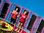 """26 JUNE 2019 - CENTRAL CITY, IOWA: Girls on the """"Black Hole"""" one of the rides at the Linn County Fair. Summer is county fair season in Iowa. Most of Iowa's 99 counties host their county fairs before the Iowa State Fair, August 8-18 this year. The Linn County Fair runs June 26 - 30. The first county fair in Linn County was in 1855. The fair provides opportunities for 4-H members, FFA members and the youth of Linn County to showcase their accomplishments and talents and provide activities, entertainment and learning opportunities to the diverse citizens of Linn County and guests.    PHOTO BY JACK KURTZ"""