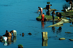 Kenyakumary, India 1994. Women washing their clothes while having a bath in a local lake.