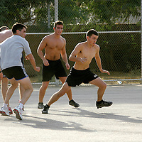 Baghdad, Iraq, 2 Oct 2005. Running 'Route Irish'...Ranger William McMaster(right) and LCPL Lewis Tennant (2nd right) playing footbal at the British embassy...B Company, 1st Battalion, The Royal Irish Regiment, a tight-knit multi national fighting force make daily escorting runs along ?Route Irish?, the infamous Baghdad Airport road. The 46 man team are all British Army regulars but come from as far afield as Fiji, South Africa and Northern and Southern Ireland. Previous deployments in Kosovo, Sierra Leone and Northern Ireland have equipped them with the valuable skills needed to provide protection for British Forces and materials transiting the world?s most dangerous highway. Due to an increased presence of US forces along the route both in dug in positions and mobile patrols, attacks along the road have slackened, despite this a day rarely passed without an IED (improvised explosive device) being detonated or a small arms attack against coalition forces. ..The convoy attempts to maintain a seclusion ?bubble? around its vehicles for the duration of the journey. Any civilian vehicle that either strays into the bubble or refuses to keep their distance represents a threat and should they ignore the warning blasts on air horns carried in each vehicle the rules of engagement progress from warning shots to use of lethal force. The relative safety of the International Zone offers them an opportunity to decompress between missions. A duty driver ferries soldiers to the ?Liberty Pool?. Once only frequented by Iraq?s Ba?athist elite the luxury swimming pool and gym now fills with troops. Their body armour, helmets and weapons all within easy reach they either soak up the sun or compete with each other in diving competitions. After a daily briefing the troops have access to the ?Mosquito and Camel? bar where they watch TV or play pool and in accordance with the ?2 can rule? are allowed to drink 2 beers per night.