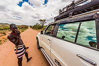 Hamer tribe man talking to the driver of a four wheel drive vehicle, Omo Valley, Ethiopia.