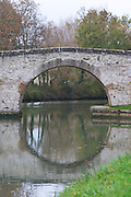 Villesequelande, near Carcassonne. Old stone bridge making a circular shape with the reflection in the water. Carcassonne. Languedoc. Canal du Midi. France. Europe.