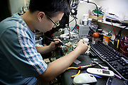 Technician fixing a computer circuit board using a soldering iron inside e-plaza digital square shopping mall. Zhongguancun or Zhong Guan Cun, is a technology hub in Haidian District, Beijing, China. It is situated in the northwestern part of Beijing city. Zhongguancun is very well known in China, and is often referred to as China's Silicon Valley. This is Beijing's computer district with numerous tech companies offices situated here amongst the many malls which sell electronics and electrons equipment of all kinds. The tech park started as a small office where two decades ago some students from a nearby university decided that computer equipment may be a thing of the future so set up a small company. It has expanded in this time to  cover many square kilometres.