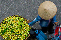 Street vendors with baskets of fresh fruit stroll the streets selling their goods in the old quarter of Hanoi.