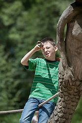 Boy standing on a ship and looking through a telescope in adventure playground, Bavaria, Germany