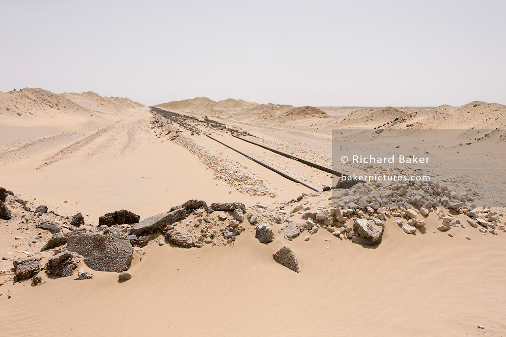A remote desert railway now missing its iron rails, stolen in the aftermath of the 2011 Egyptian revolution, near Bagdad, Kharga Oasis, Western Desert, Egypt. The desert lies in the New Valley Governorate, 350 km (220 mi.) and measures approximately 80 km (50 mi) from east to west and 25 km (16 mi) from north to south and is now patrolled by armed police convoys.