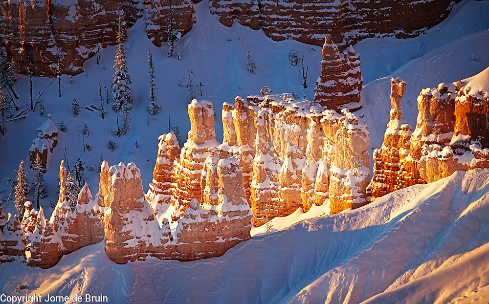 A red rock formation in Bryce Canyon bathing in early morning light.