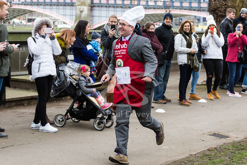 MPs and members of the House of Lords compete in the annual Rehab pancake race, a relay of eleven laps in Victoria Tower Gardens adjacent to the Houses of Parliament in London. The race is held every year on Shrove Tuesday and was won by the Media team. PICTURED: The Daily Telegraph's Chris Hope completes his lap. London, February 13 2018.