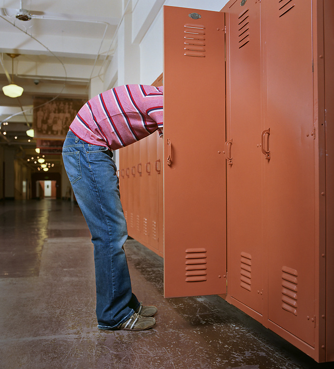 Male high school student sticking head in school locker, side view