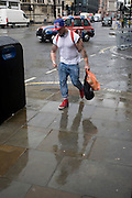 A man with tattooed arms dashes through seasonal rain showers in central London.