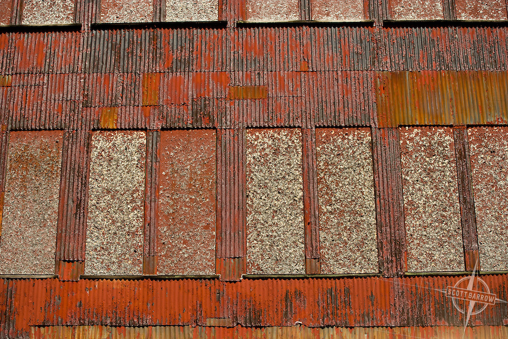 Wearhouse building in Pittsfield, MA. Corrugated steel with peeling paint. Red.
