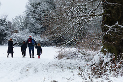 A family enjoys a walk in the snow as people and their pets enjoy the three inches of snow on Hampstead Heath in North London. Hampstead, London, February 01 2019.