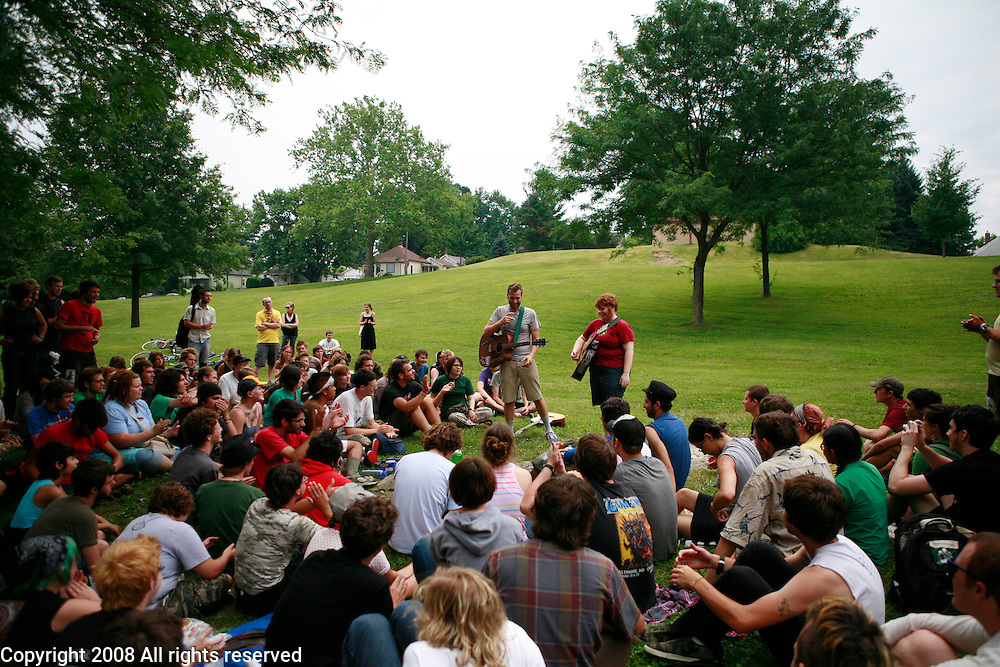 A group gathering on Sunday for an acoustic punk show during the Plan-It-X Festival. Paul Baribeau and Ginger Alford are playing folk/rock songs by Bruce Springsteen.