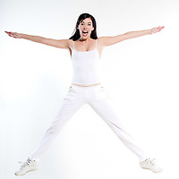 beautiful young woman exercising workout stretching jumping happy on studio isolated white background