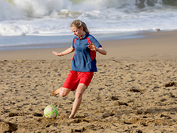 Girl playing with soccer ball on the beach