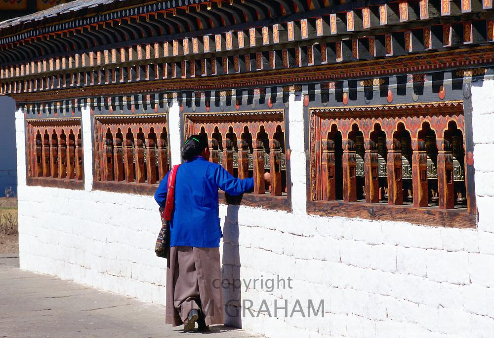 Bhutanese woman touching prayer bells while praying at the Tashichho Dzong in Bhutan