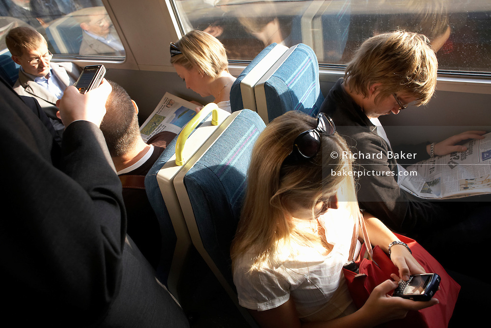 Rush hour train commuters check messages on-board carriages travelling into city mainline stations in south London.