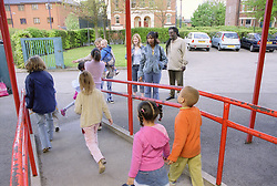Single parents waiting outside primary school to collect children,