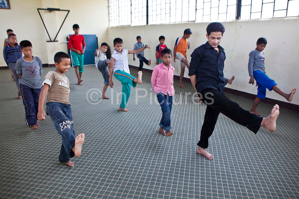Young Nepalese boys practice yoga in the Voice for Children rehabilitation center in Kathmandu, Nepal.  The not-for-profit organisation supports street children and those who are at risk of sexual abuse through educational and vocational training opportunities, health services and psychosocial counseling.  These young children have recently been found by the charity and attend the children's drop-in centre where they play games and activities including yoga classes.