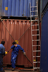 Bosun Sami Tartoussi, of Lebanon, takes a break from tightening the lashings on the containers as they are loaded onto the vessel in Port Said, Egypt on April 9, 2008. The Bisanzio, a feeder ship taking containers from Port Said to Beirut, is Lebanese owned, has three different nationalities aboard, and flies a St. Vincent flag. The Suez Canal is one of the most important shipping routes in the world, as it allows allows two-way water transportation - most importantly between Europe and Asia without the circumnavigation of Africa.