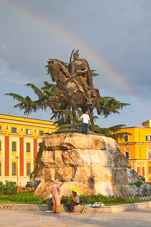 The statue of the 15th century warrior and national hero Skanderburg Skanderbeg on a huge stone base. A colourful rainbow in the sky and administrative buildings in the background. The Tirana Main Central Square, Skanderbeg Skanderburg Square. Tirana capital. Albania, Balkan, Europe.