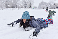 © Licensed to London News Pictures. 10/12/2017. London, UK. A girl enjoys sledding on a snow covered golf course as snow falls in Northwood, north west London.  The weather forecast predicts an accumulation of three to four inches with snow continuing to fall well into the afternoon.  Photo credit: Stephen Chung/LNP