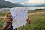 Asia, Nepal, young boy hold a letter with a plea for money to buy a football