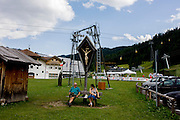 Visitors rest beneath a large crucifix in the town of Corvara during the summer walking season in south Tyrol, northern Italy.