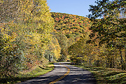 On the Blue Ridge Parkway, view brilliant fall colors in mid October, in North Carolina, USA. This photo is at Blue Ridge Parkway Milepost 455 in the Plott Balsam Range, within the Qualla Boundary between Soco Creek and Soco Gap. The Qualla Boundary is a land trust supervised by the United States Bureau of Indian Affairs for the Tribe of the Eastern Band of the Cherokee Indians, who reside on the adjacent Reservation in western North Carolina. The 469-mile Blue Ridge Parkway was built 1935-1987 to aesthetically connect Shenandoah National Park (in Virginia) with Great Smoky Mountains National Park in North Carolina. (The Smokies are a subrange of the Blue Ridge Mountains, part of the Appalachian Mountains.)