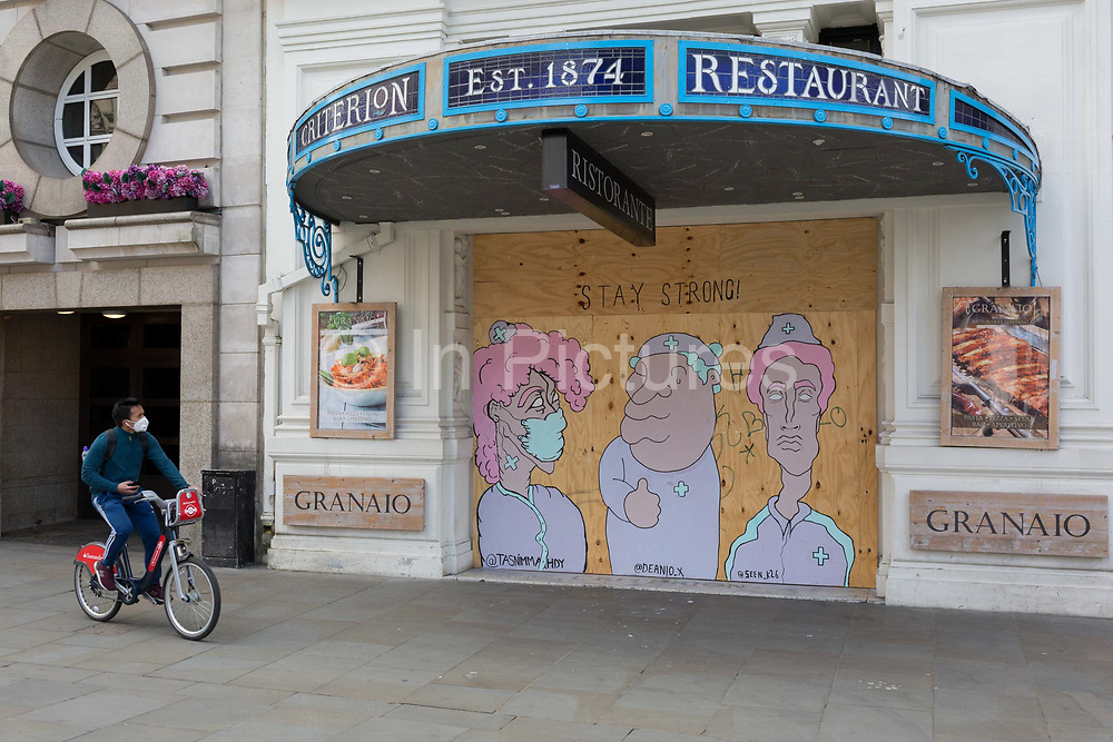 As it is reported that a further 428 people have died with Covid-19 in the UK, the total number of deaths in hospitals and the wider community to 33,614, street art by three artists has been created on the plyboard sheeting of the still closed Criterion Restaurant opposite Eros in  in Leicester Square, on 14th May 2020, in London, England. The Criterion Restaurant is an opulent restaurant complex facing Piccadilly Circus in the heart of London. It was built by architect Thomas Verity in Neo-Byzantine style for the partnership Spiers and Pond, which opened it in 1873. It is a Grade II* listed building and is in the Top 10 most historic and oldest restaurants in the world.