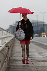 © Licensed to London News Pictures. 10/05/2016. LONDON, UK.  A woman is caught in a heavy rain shower as she crosses Waterloo Bridge in central London this morning.  Photo credit: Vickie Flores/LNP