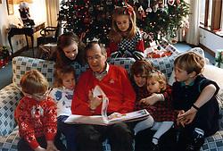 Dec. 24, 1991 - Camp David, Maryland, United States of America - Camp David, Maryland - December 24, 1991 -- United States President George H.W. Bush reads a Christmas story to his grandchildren, Pierce Bush, Marshall Bush, Barbara Bush (daughter of George W. Bush), Lauren Bush, Jenna Bush (daughter of George W. Bush), Ashley Bush and Sam LeBlonde at Camp David in Maryland on Christmas Eve, December 24, 1991..Credit: White House via CNP (Credit Image: © White House/CNP/ZUMAPRESS.com)