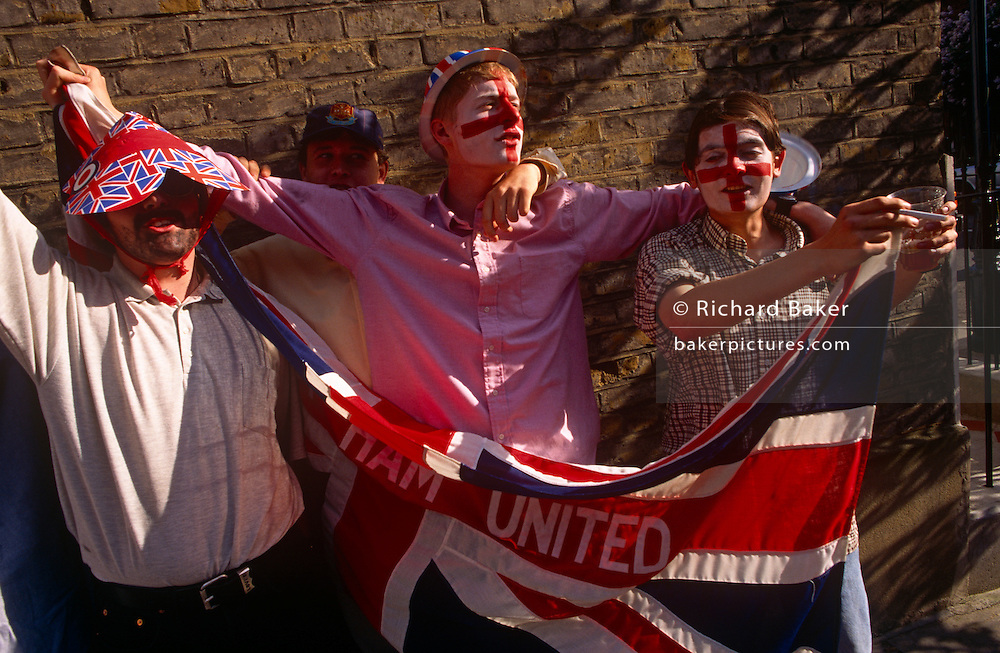 During a street party in London's East End, the young men have decided to parade outside with their flag to show their devotion to their local club. One reaches down to pick up a patriotic hat during the celebrations commemorating the 50th anniversary of VE (Victory in Europe) Day on 6th May 1995. West Ham was founded in 1895 as Thames Ironworks FC and reformed in 1900 as West Ham United. In 1904 the club relocated to their current Boleyn Ground stadium and will take over the 2012 Olympic stadium. In the week near the anniversary date of May 8, 1945, when the World War II Allies formally accepted the unconditional surrender of the armed forces of Germany. Street parties now - as they did in 1945 - played a large part in the country's patriotic well being.