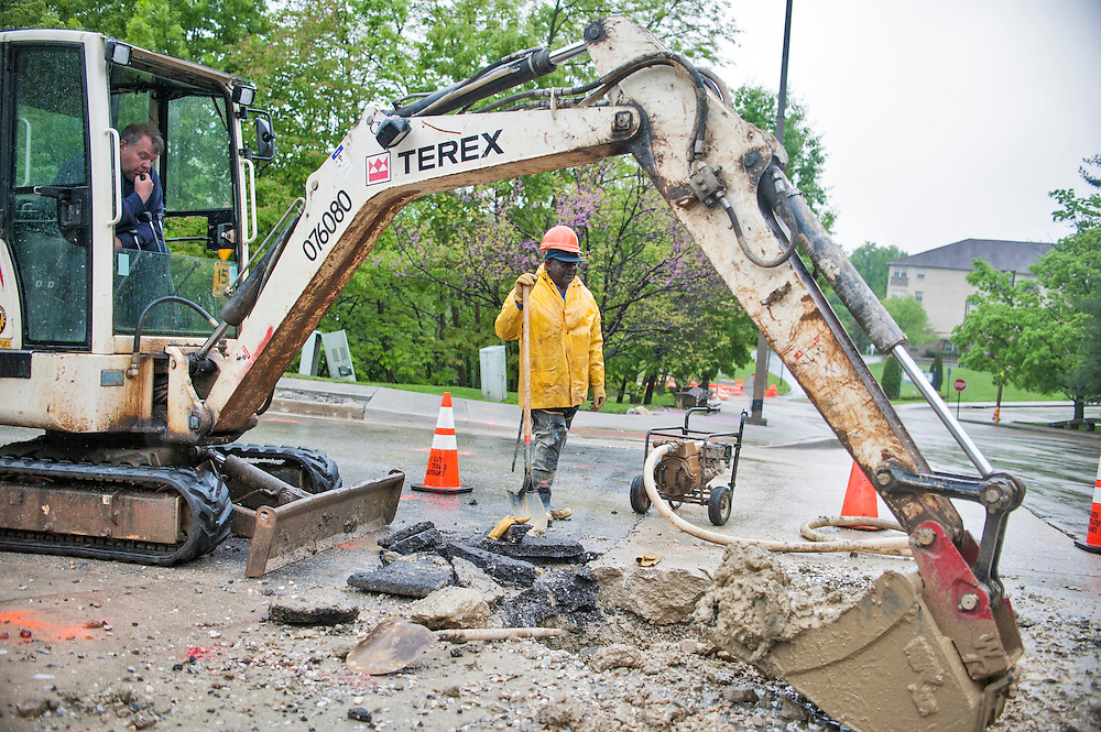 Photo by Matt Roth<br /> <br /> Kevin Koluch, backhoe operator, and Edward Woolfolk, a utility repair II, both Baltimore City Department of Public Works employees, respond to a water main break at the intersection of Yellowwood Ave. and Springfield Dr. in Baltimore, Maryland on Tuesday, May 07, 2013.