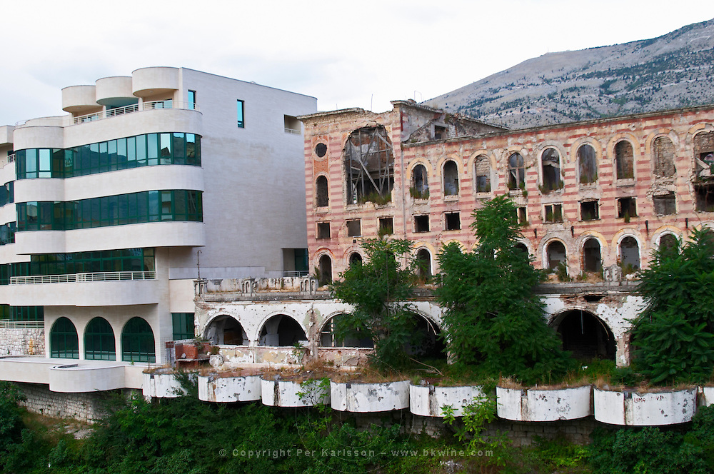 Building in Mostar damaged by the war and still not renovated. Ruined by bullet holes, mortar bomb shell grenade damage, very close to the beautifully renovated old town city centre. Musala area as seen from the west side of the Neretva River. Tito's Villa (left) and the Neretva Hotel (right) severely damaged. Tito's villa, restored. Town of Mostar. Federation Bosne i Hercegovine. Bosnia Herzegovina, Europe.