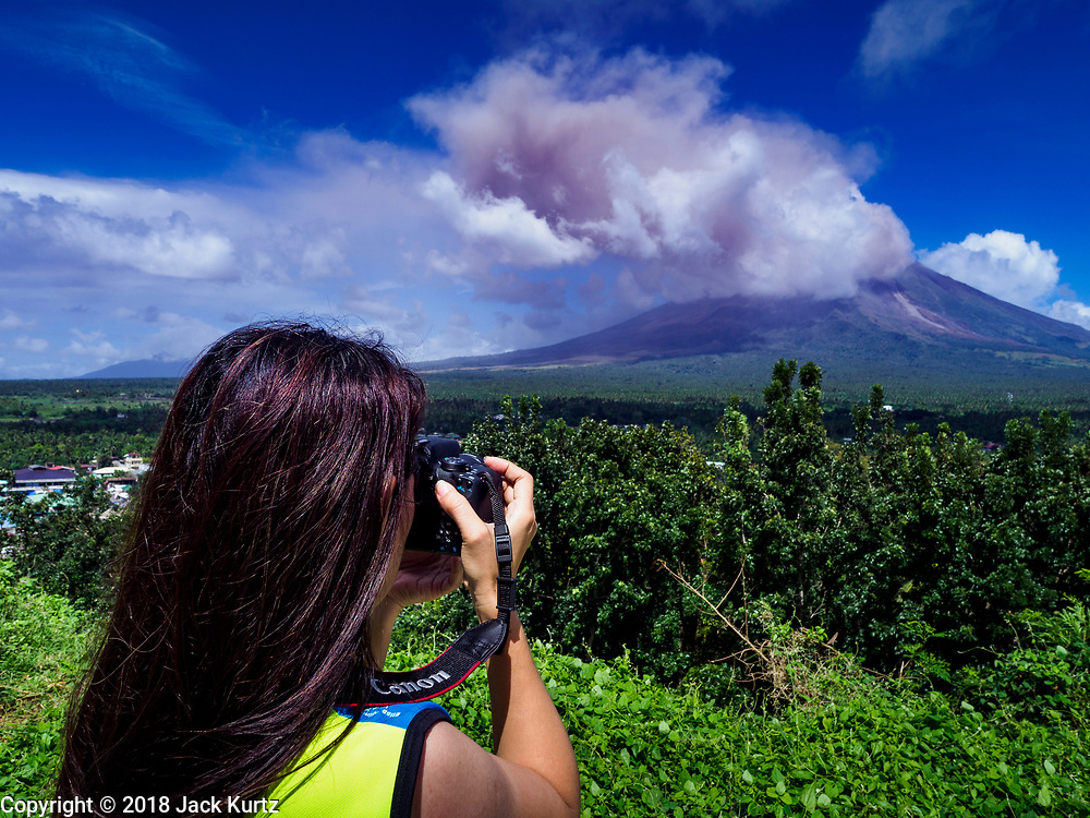 """22 JANUARY 2018 - CAMALIG, ALBAY, PHILIPPINES: A woman takes pictures of an eruption of the Mayon volcano. There were a series of eruptions on the Mayon volcano near Legazpi Monday. The eruptions started Sunday night and continued through the day. At about midday the volcano sent a plume of ash and smoke towering over Camalig, the largest municipality near the volcano. The Philippine Institute of Volcanology and Seismology (PHIVOLCS) extended the six kilometer danger zone to eight kilometers and raised the alert level from three to four. This is the first time the alert level has been at four since 2009. A level four alert means a """"Hazardous Eruption is Imminent"""" and there is """"intense unrest"""" in the volcano. The Mayon volcano is the most active volcano in the Philippines. Sunday and Monday's eruptions caused ash falls in several communities but there were no known injuries.    PHOTO BY JACK KURTZ"""