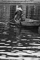One woman wearing a traditional conical hat in a boat on the Thu Bon river in Hoi An, Vietnam.