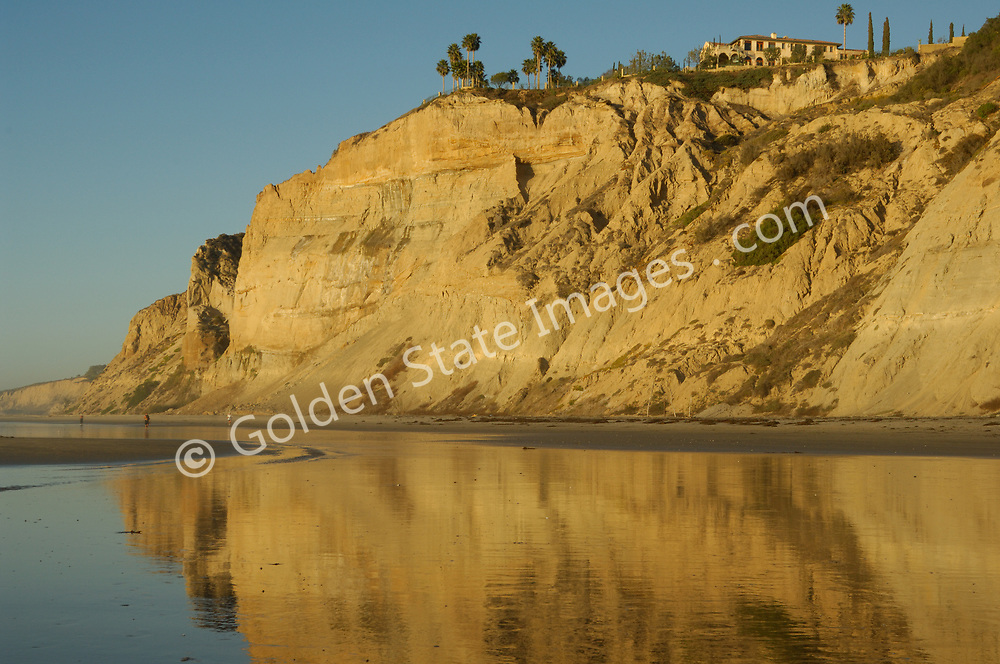Cliffs reflected on tidal flats by the late afternoon light.