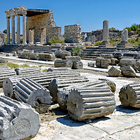 Miletus. Turkey.  View of abandoned Ionic column drums in front of the partially restored Ionic Stoa which was built in 50 AD by Emperor Tiberius Claudius Sophanes. The Ionic Stoa originally had thirty five Ionic columns in front and nineteen shops at the rear.