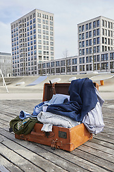 Open suitcase full of clothing on floorboard in playground, Munich, Bavaria, Germany