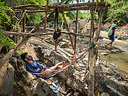 17 JUNE 2016 - DON KHONE, CHAMPASAK, LAOS: A fisherman rests while another walks to work near Khon Pa Soi Waterfalls, on the east side of Don Khon. It's the smaller of the two waterfalls in Don Khon. Fishermen have constructed an elaborate system of rope bridges over the falls they use to get to the fish traps they set. Fishermen in the area are contending with lower yields and smaller fish, threatening their way of life. The Mekong River is one of the most biodiverse and productive rivers on Earth. It is a global hotspot for freshwater fishes: over 1,000 species have been recorded there, second only to the Amazon. The Mekong River is also the most productive inland fishery in the world. The total harvest of fish from the Mekong is approximately 2.5 million metric tons per year. By some estimates the harvest in the Tonle Sap (in Cambodia) had doubled from 1940 to 1995, but the number of people fishing the in the lake has quadrupled, so the harvest per person is cut in half. There is evidence of over fishing in the Mekong - populations of large fish have shrunk and fishermen are bringing in smaller and smaller fish.        PHOTO BY JACK KURTZ